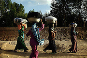 Women are walking home after washing clothes next to a small river in Bamyan, Afghanistan. In the town there is no electricity or running water. Power is only being provided by generators or solar panels. The Buddhas of Bamiyan were two 6th century monumental statues of standing Buddhas carved into the side of a cliff in the Bamiyan valley in the Hazarajat region of central Afghanistan, situated 230 km northwest of Kabul at an altitude of 2500 meters. The statues represented the classic blended style of Gandhara art. The main bodies were hewn directly from the sandstone cliffs, but details were modelled in mud mixed with straw, coated with stucco. Amid widespread international condemnation, the smaller statues (55 and 39 meters respectively) were intentionally dynamited and destroyed in 2001 by the Taliban because they believed them to be un-Islamic idols. Once a stopping point along the Silk Road between China and the Middle East, researchers think Bamiyan was the site of monasteries housing as many as 5,000 monks during its peak as a Buddhist centre in the 6th and 7th centuries. It is now a UNESCO Heritage Site since 2003. Archaeologists from various countries across the world have been engaged in preservation, general maintenance around the site and renovation. Professor Tarzi, a notable An Afghan-born archaeologist from France, and a teacher in Strasbourg University, has been searching for a legendary 300m Sleeping Buddha statue in various sites between the original standing ones, as documented in the old account of a renowned Chinese scholar, Xuanzang, visiting the area in the 7th century. Professor Tarzi worked on projects to restore the other Bamiyan Buddhas in the late 1970s and has spent most of his career researching the existence of the missing giant Buddha in the valley.