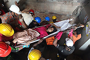 Garments Factory Collapse – APR. 24, 2013 – A group of firefighter's rescue a garments worker who trap on the nine store collapse building. The building collapse occurred in Savar, a town of the national capital, Dhaka, and is the latest accident to badly affect Bangladesh's garment industry. At least 1200 people were killed many more trapped inside a mountain of jumbled concrete debris and over 2,400 injured in Savar on the outskirts of the capital on 24 April 2013 Wednesday morning when a nine-storey building housing five garment factories collapsed. Rescuers fear the death toll may rise significantly. Local citizen, fire fighters and army personnel joined police and volunteers to rescue those trapped under the debris. A number of workers of four garment factories in Savar alleged that they were forced to work in the morning. © Monirul Alam