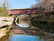 Narrows Covered Bridge was built in 1882 in Burr Arch style by J.A. Britton. Walk across this bridge in Turkey Run State Park, in historic Parke County, Indiana, USA. Sugar Creek reflects the covered bridge plus the concrete arch of the modern highway bridge seen behind.