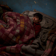 A young migrant sleeps wrapped in blankets in one of the abandoned warehouses in central Belgrade. Due to the extreme low temperatures typical of a Serbian winter, many migrants spend the days by the fire or wrapped under blankets.
