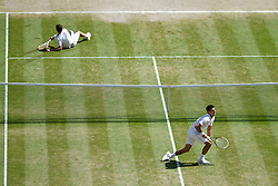 LONDON, ENGLAND - Friday, July 4, 2014: Grigor Dimitrov (BUL) and Novak Djokovic (SRB) pick themselves up after ending up on the floor during the Gentlemen's Singles Semi-Final match on day eleven of the Wimbledon Lawn Tennis Championships at the All England Lawn Tennis and Croquet Club. (Pic by David Rawcliffe/Propaganda)
