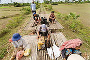 "01 JULY 2006 - PHNOM PENH, CAMBODIA: The bamboo train in back pushes the bamboo train in front after the first one ran out of gas on the tracks in central Cambodia. The ""bamboo trains"" run along the government tracks in rural Cambodia. Bamboo mats are fitted over wheels which ride on the rails. The contraption is powered by a either a motorcycle or lawn mower engine. The Cambodian government would like to get rid of the bamboo trains, but with only passenger train in the country, that runs only one day a week, the bamboo trains meet a need the government trains do not. While much of Cambodia's infrastructure has been rebuilt since the wars which tore the country apart in the late 1980s, the train system is still in disrepair. There is now only one passenger train in the country. It runs from Phnom Penh to the provincial capitol Battambang and it runs only one day a week. It takes 12 hours to complete the 190 mile journey.  Photo by Jack Kurtz / ZUMA Press"