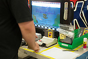 An employee tests refurbished games on a Nintendo NES at the GameStop retro classics console games refurbishment center in Grapevine, Texas on June 24, 2015. (Cooper Neill for Mashable)