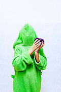 person covered in a bright green hoodie holds a cabbage
