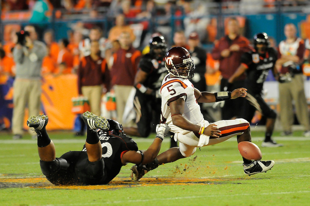 January 1, 2009: Tyrod Taylor of the Virginia Tech Hokies fumbles after the hit from John Hughes of the Cincinnati Bearcats during the NCAA football game between the Virginia Tech Hokies and the Cincinnati Bearcats in the Orange Bowl Classic. The Hokies defeated the Bearcats 20-7.