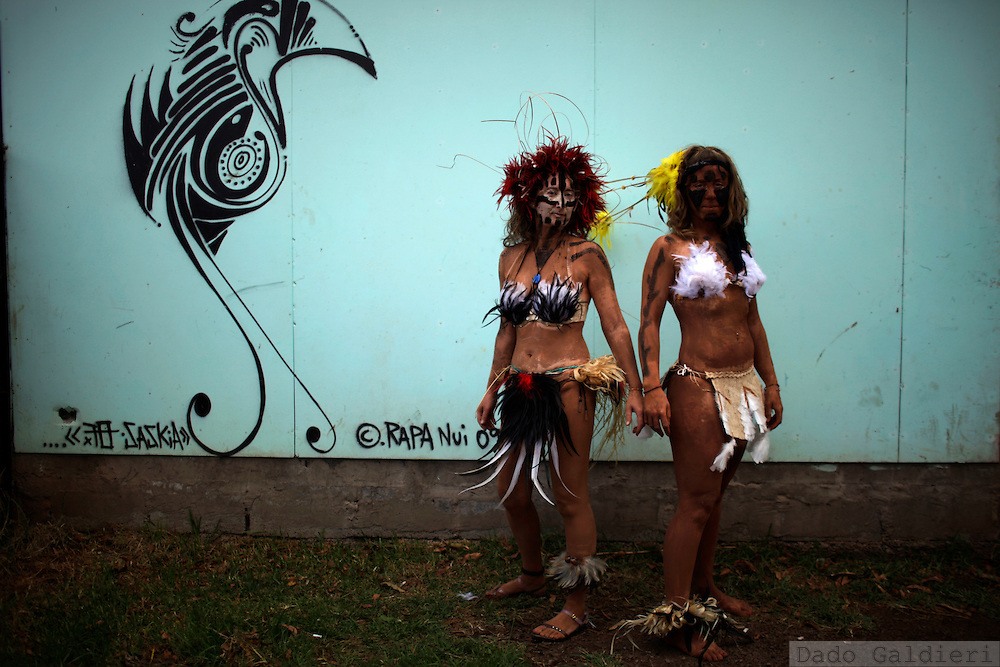 Two foreign tourists display their body tattooed in volcanic mud, an ancestral technique, as they poses for a photo aside a stylized graffiti depicting a bird, symbol of the Rapa Nui culture during a festival named Tapati Rapa Nui in Hanga Roa, Rapa Nui, Saturday, Feb. 12, 2011. As Chile  tries to push globalization into the island with the same power the Pacific waves reach its rocky shores, boundaries of race become blurrier in the most important Polynesian island, and during the Tapati festival, a former native week long celebration, only blue eyed or really white skinned people can be spotted like foreigners.