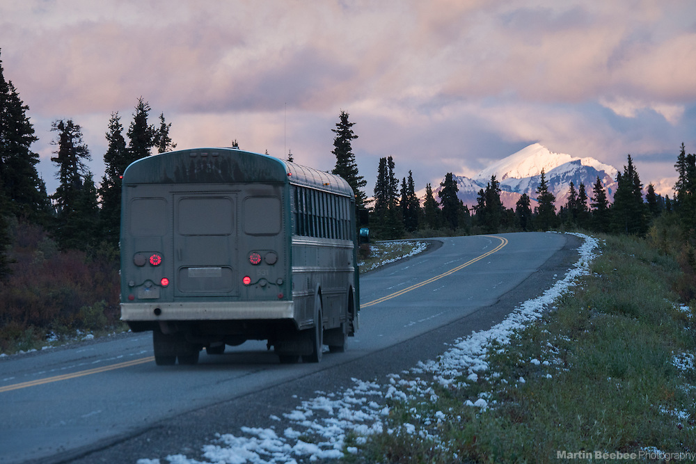 Park bus driving on the main road in Denali National Park at sunset, Alaska