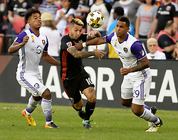 September 9, 2017 - Washington, DC, USA - 20170909 - D.C. United midfielder LUCIANO ACOSTA (10) plays the ball forward between Orlando City FC midfielder CRISTIAN HIGUITA (7) and Orlando City FC defender TOMMY REDDING (29) in the first half at RFK Stadium in Washington. (Credit Image: © Chuck Myers via ZUMA Wire)