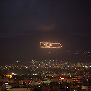 An illuminated flag of the Turkish Republic of Northern Cyprus is seen overlooking Nicosia March 12, 2014. This year marks 40 years since the Cyprus National Guard staged a coup in Cyprus and the subsequent Turkish military intervention, which escalated a civil war between the Greek and Turkish Cypriot communities on the island. After the ceasefire a heavily restricted UN controlled Buffer Zone between the north and south of the island was put into operation. It stretches 180 Km across the whole island measuring 7.4 km at its widest and 3.3 meters at its narrowest point. It is restricted to the general public and no Greek or Turkish Cypriots are allowed inside. REUTERS/Neil Hall (BRITAIN)