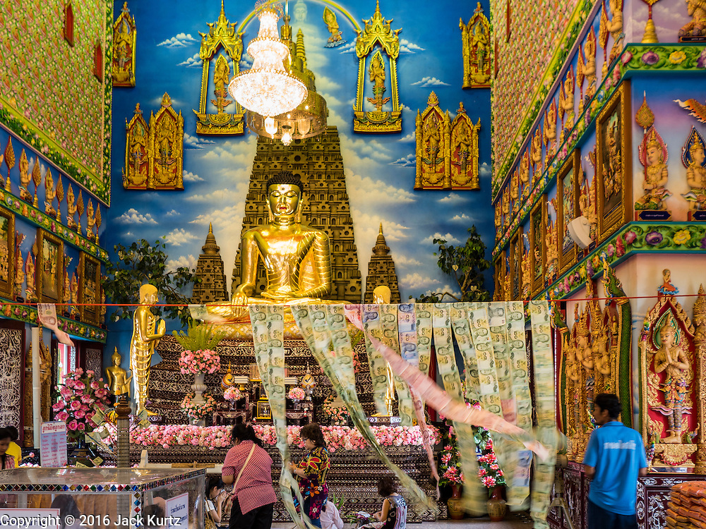 """30 JANUARY 2016 - NONTHABURI, NONTHABURI, THAILAND: Inside the """"viharn,"""" or main prayer hall, at Wat Bua Khwan, a large Buddhist temple in Nonthaburi, north of Bangkok, Thailand. The money hanging in the center is donations from people who come to the temple.         PHOTO BY JACK KURTZ"""