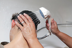Single parent helping her daughter wash her hair using a shower head,