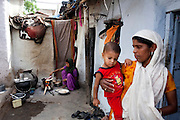 Sadma Khan (in purple), 19, makes lunch in the shared compound of her mother's (in orange) extended family's house in a slum area of Tonk, Rajasthan, India, on 19th June 2012. She was married at 17 years old to Waseem Khan, also underaged at the time of their wedding. The couple have an 18 month old baby (in red) and Sadma is now 3 months pregnant with her 2nd child and plans to use contraceptives after this pregnancy. She lives with her mother since Waseem works in another district and she can't take care of her children on her own. Photo by Suzanne Lee for Save The Children UK