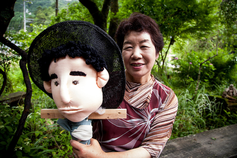 MIYOSHI, JAPAN - JULY 11 :  Tsukimi Ayano holding a hand made dolls in front of her house in Nagoro village, Miyoshi, Japan on July 11, 2015. Nagoro is a slowly shrinking village located in the valleys of Shikoku, Japan. According to Japan's Statistic Bureau, the percentage of people over 65 years old in Japan is 26.8% while that of the the world is 8.2%. The National Institute of Population and Social Security Research in Tokyo, Japan's population, now around 128 million, is expected to dip below 100 million in 2046.<br /> <br /> Photo: Richard Atrero de Guzman