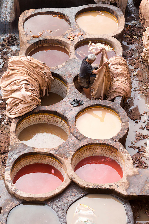 FEZ, MOROCCO - 3rd DECEMBER 2016 - Workers dye animal hides in the tannery vats at the Chouwara Tannery, old Fez Medina, Middle Atlas Mountains, Morocco.