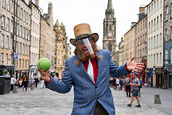Edinburgh, Scotland, UK. 7 August, 2020. On what would have been the opening day of the cancelled 2020 Edinburgh Fringe Festival, street performer and magician, Dr Love prepares to entertain the public on the Royal Mile in the Old Town. He was wearing PPE and  observing strict social distancing rules and performing within a cordoned off area to prevent crowds from forming. Iain Masterton/Alamy Live News