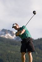 A male golfer tees off on the Whistler Golf Course, Whistler, BC Canada with Whistler Mountain in the background.