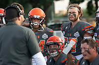 KELOWNA, BC - AUGUST 3:  Coach Jamie Boreham stands on the sidelines and goes over a play with Gabe Loster #44, Christian Horner #57 and Aiden Hennessey #45 of the Okanagan Sun against the Kamloops Broncos at the Apple Bowl on August 3, 2019 in Kelowna, Canada. (Photo by Marissa Baecker/Shoot the Breeze)