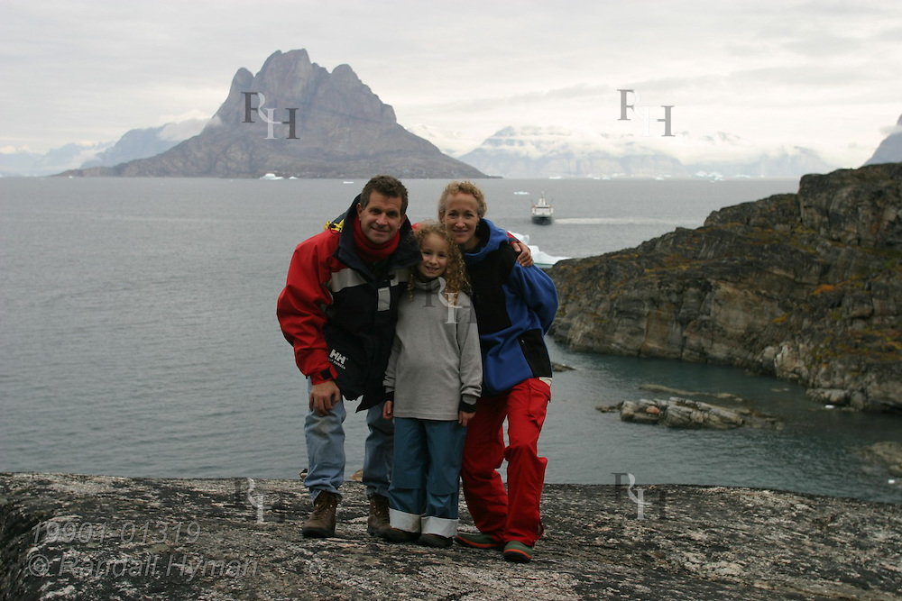 Family from expedition cruise ship Clipper Adventurer poses above cove at Qilakitsoq on the Nuussuaq Peninsula with Uummannaq Island behind them in distance; Greenland