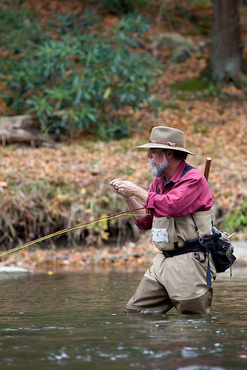 Penns Creek fly fishing guide, Tom  Doman ties on a fly while fishing for trout on Penns Creek, Pennsylvania