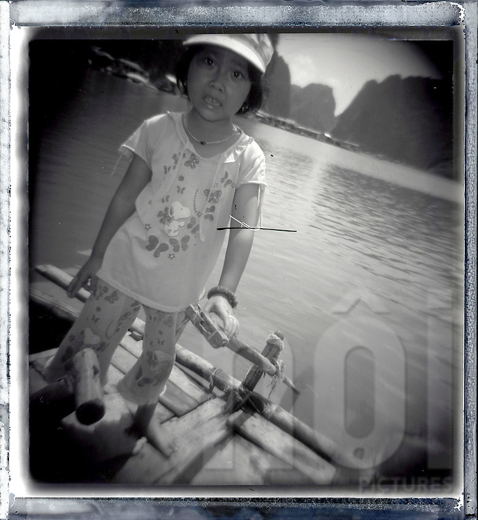 Portrait of a little girl sailing on a tiny barge in Halong bay. Halong bay, Quang Ninh province, Vietnam, Asia.