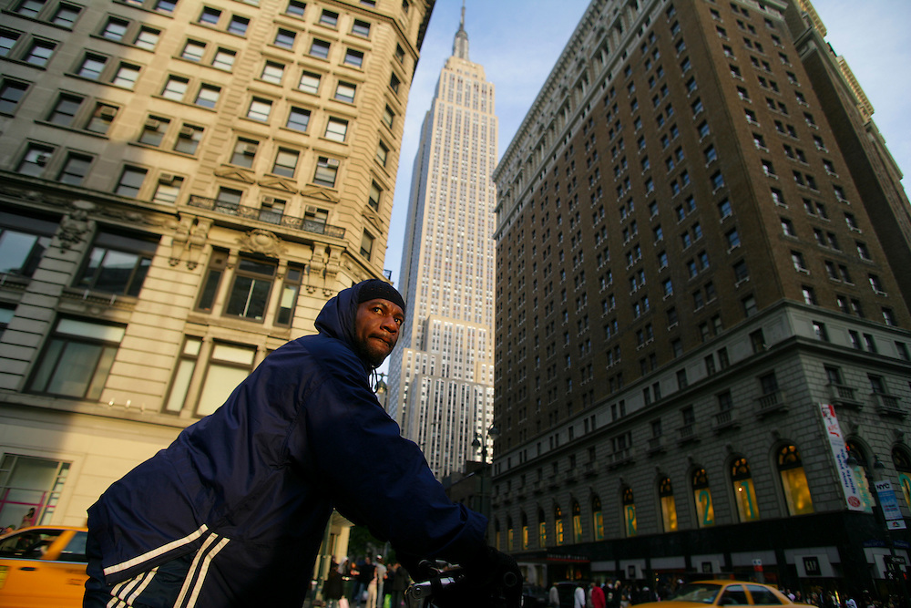 A man waits in his bycicle on a red light with the Empire State Building in the background.