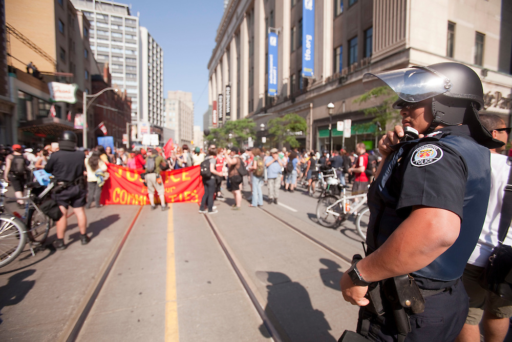Protestors, flanked by police, march through the streets of Toronto, Canada, June 25, 2010 as the G8 leaders gather in Huntsville, Ontario.<br /> AFP/GEOFF ROBINS/STR