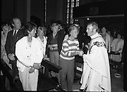 "Fr Niall O'Brien says Thanksgiving Mass.1984..16.07.1984..07.16.1984..16th July 1984..In celebration of his safe homecoming from the Philippines,Fr Niall O'Brien said a thanksgiving mass At Newtownpark Ave,Blackrock,Dublin. Along with two other priests and six lay people,Fr Niall was falsly accused of multiple murders.They became known as ""The Negros Nine"".After President Reagan visited Ireland,The American government put pressure on the Marcos regime and all charges were dropped and all were fully exonerated...Image taken as Fr O'Brien shakes the hands of some of the congregation in the ""Peace Be with you"" part of the Mass...Note; Fr O'Brien, who was born in Dublin in 1939,died in Pisa, Italy in 2004"