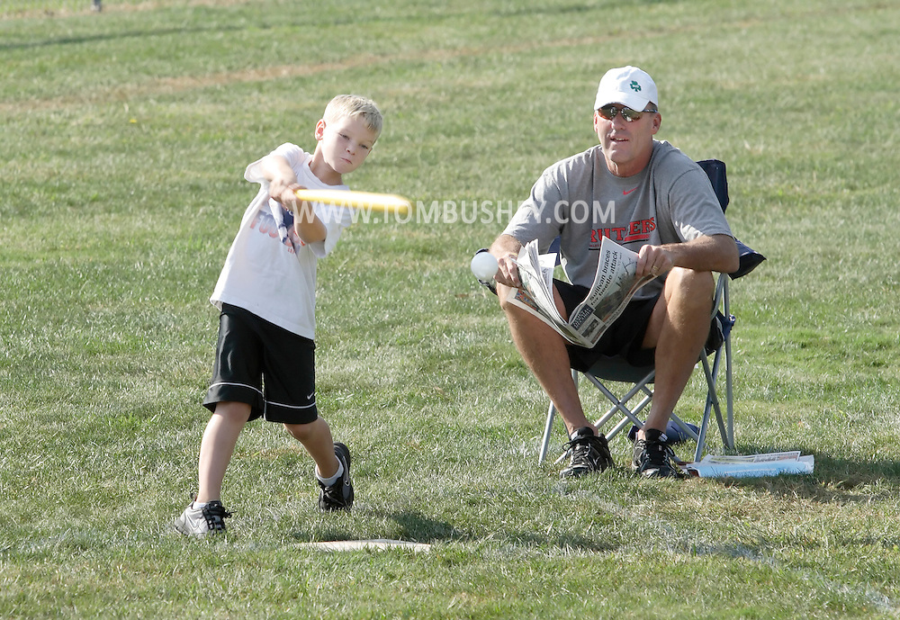 Scotchtown, New York - A young boy swings at a pitch as a man sits in a chair with a newspaper while they wait to play in the Wiffle for Kids charity Wiffle Ball tournament at the Town of Wallkill Little League fields on Sept. 25, 2010. Wallkill East Rotary. ©Tom Bushey / The Image Works