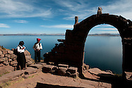 Two boys relax near an arch erected on Taquile Island on the Peruvian side of Lake Titicaca.  The island is known for it's textiles and weavings and is situated within view of the Bolivian shore, at more than 12,000 feet above sea level.