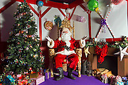 A comical feature showing the diverse and wide variety of Santa Clause's one can find in and around London. Father Christmas seems to have a wide range of appearances and different types of grottos from the elaborate Hamley's Toy Store to a garden shed in a Chobham garden centre. <br /> Pictured - Santa Clause and his grotto at Squires Garden Centre, Farnham.<br /> Credit: Rick Findler / Story Picture Agency