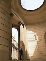 Businessman using mobile phone in neo-classical style building
