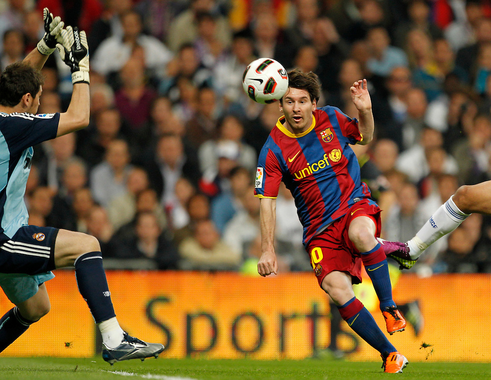 Real Madrid's goalkeeper Iker Casillas, left, vies for the ball with Barcelona's Lionel Messi from Argentina, right, during their Spanish La Liga soccer match at the Santiago Bernabeu stadium in Madrid, Saturday, April 16, 2011.