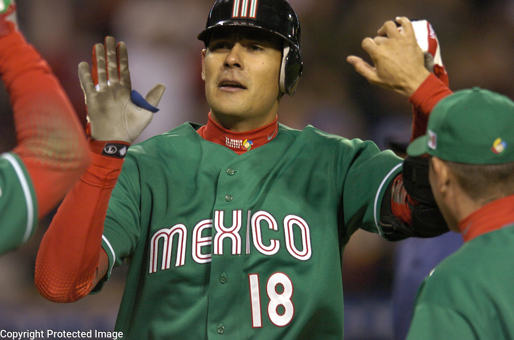 Team Mexico's Luis Alfonso Garcia is congratulated after his homerun against Team Korea in Round 2 action at Angel Stadium of Anaheim.