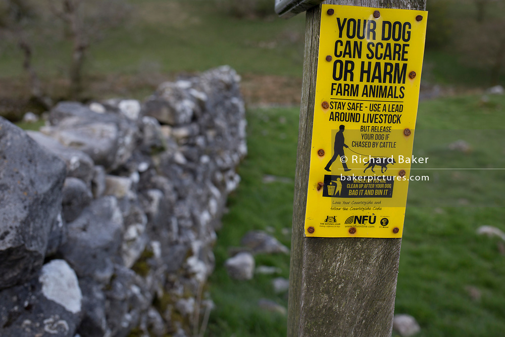A warning sign for dog owners to keep animals on leads and preventing attacks on livestock, on a gate on farm land in the Yorkshire Dales National Park, on 12th April 2017, in Malham, Yorkshire, England.