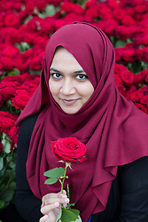 "© Licensed to London News Pictures. 11/06/2017. LONDON, UK.  Sara Lutfullah from south London poses for a photograph on London Bridge with a red rose. 1,000 red roses with messages of ""love and solidarity"" were given to passers by on London Bridge today.  Photo credit: Vickie Flores/LNP"