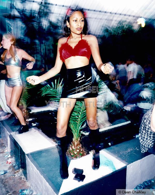 Woman dancing on a stage wearing a black PVC mini skirt Ibiza 1998