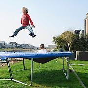 Nederland Amsterdam 29 maart 2011 20110329 Nieuwbouwwijk Ijburg, kinderen spelen, zij springen op een trampoline, in de achtertuin van een van de grote woningen met individuele architectuur die aan het water grenzen. Individueel vormgegeven architectuur. Noot: Fotograaf heeft toestemming gekregen van volwassene op de achtergrond om de beelden te maken.  , stadsuitbreiding, stadswijk, sunny, sunshine, vastgoed, ventje, ventjes, vernieuwing, vinex, vinex-locaties, vinex-wijken, vinexbuurt, vinexlocatie, vinexlokatie, vinexwijk, voorgevel, voorjaar, vrij, vrije tijd, warm weer, water, waterwoning, waterwoningen, wijk, wijken, wonen, woning, woningbehoefte, woningen, woningmarkt, woningvoorraad, woonbuurt, woonbuurten, woonlast, woonlasten, woonwijk, woonwijken, woz waarde, Youth, zichzelf vermaken, zonlicht, zonnetje, zonnig, zonnig weer, zonnige dag, zweven Foto: David Rozing