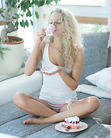 Woman with raspberry cake enjoying coffee while sitting on sofa in house