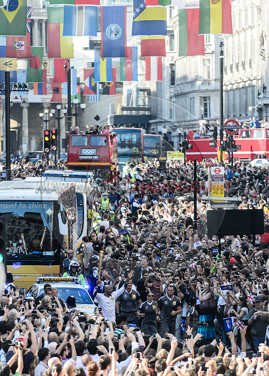 LONDON, ENGLAND, JULY 26, 2012: Crowds line the eastern avenue of Regent Street to watch torch bearer and former Olympic silver medallist Frank Fredericks of Namibia carry the Olympic flame as it makes its way through central London on July 26, 2012.
