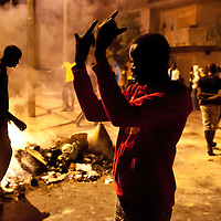 A young police with an insulting gesture on sunday February 20 after an unrest faced by police and opposition to the candidacy of outgoing President Wade and the death of a young man in the neighborhood of Rufisque protesters lit fires in several parts of the city. © Sylvain Cherkaoui