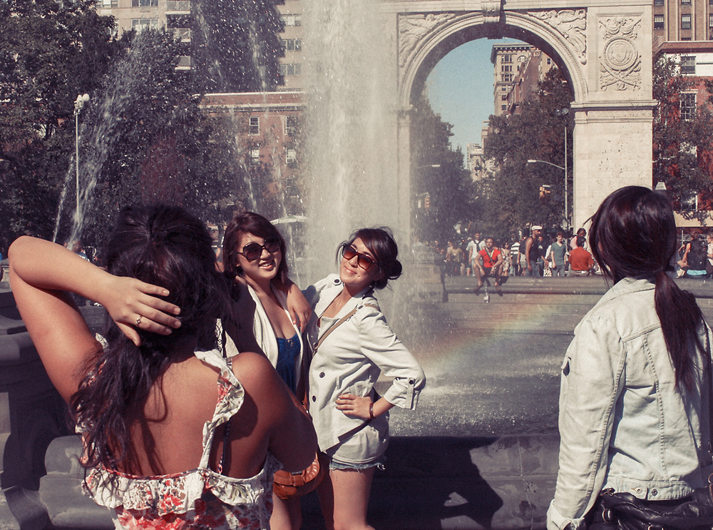 Pretty Asian girls posing by fountain in Washington square park. NYC 2010