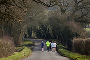 Joggers keeping fit out jogging in country lane, Bourton-on-the-Water , The Cotswolds, United Kingdom