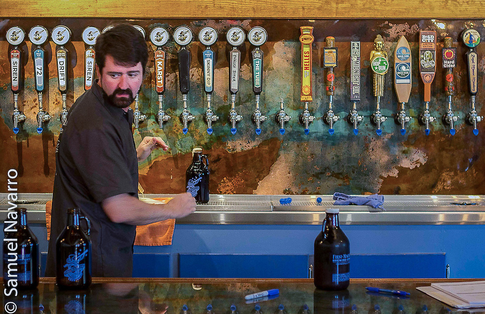 Inside First Magnitude's taproom, Denny fills up three 32-ounces beer containers to take on a business trip to Jacksonville, Florida, to meet with local craft beer brewery owners. (photo by Samuel Navarro)