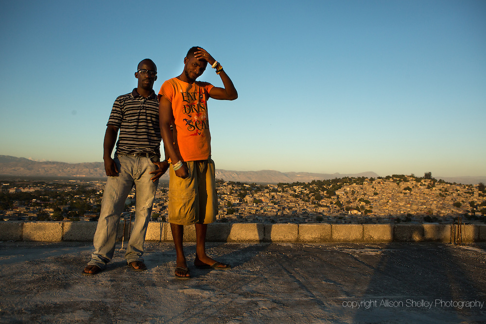 "Horlich Florestal, 29, L, and Rosemond Altidon, 27, R, stand on the roof of their apartment building, half of which was destroyed in the earthquake of January 12, 2010, in the Fort National neighborhood of Port-au-Prince, January 4, 2015.  They both still live in the building, and Alton helped convert the building's ragged edges into a balcony. Said Florestal, ""I was completely scared when that quake happened because I had never felt an earthquake before.  Many of my neighbors, including two cousins and their aunt, died when our building fell apart.  I didn't know if life would continue.  Everything was gone.  Life was gone."""