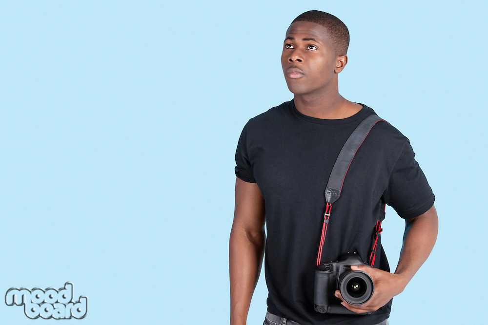 Young African American man with digital camera looking up over blue background