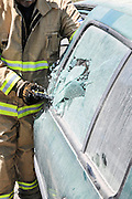 Firefighter uses an axe to break a car's side window to rescue the trapped driver and passengers