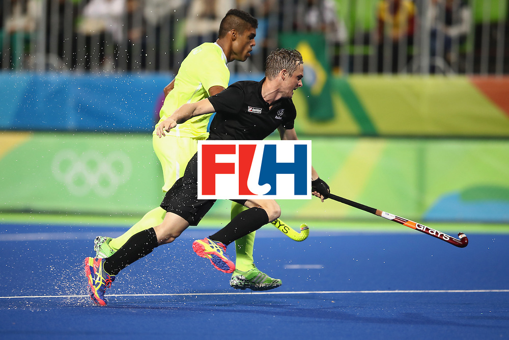 RIO DE JANEIRO, BRAZIL - AUGUST 10:  Hugo Inglis of New Zealand and Bruno Mendonca of Brazil compete for the ball during the men's pool A match between New Zealand and Brazil on Day 5 of the Rio 2016 Olympic Games at the Olympic Hockey Centre on August 10, 2016 in Rio de Janeiro, Brazil.  (Photo by Mark Kolbe/Getty Images)