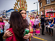 "29 APRIL 2017 - MINNEAPOLIS, MINNESOTA: A participant in the parade gets a congratulatory hug during the parade at Songkran Uptown. Several thousand people attended Songkran Uptown on Hennepin Ave in Minneapolis for the city's first celebration of Songkran, the traditional Thai New Year. Events included a Thai parade, a performance of the Ramakien (the Thai version of the Indian Ramayana), a ""Ladyboy"" (drag queen) show, and Thai street food.     PHOTO BY JACK KURTZ"