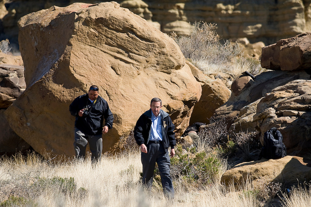 041612       Brian Leddy.Office of Medical Investigator Richard Malone and McKinley County Sheriff's Office Investigator Joseph Guillen work the scene where a body was found behind the area of the Rio West Mall Monday morning. Two passerby said they spotted the body of male curled up among the rocks and called police.