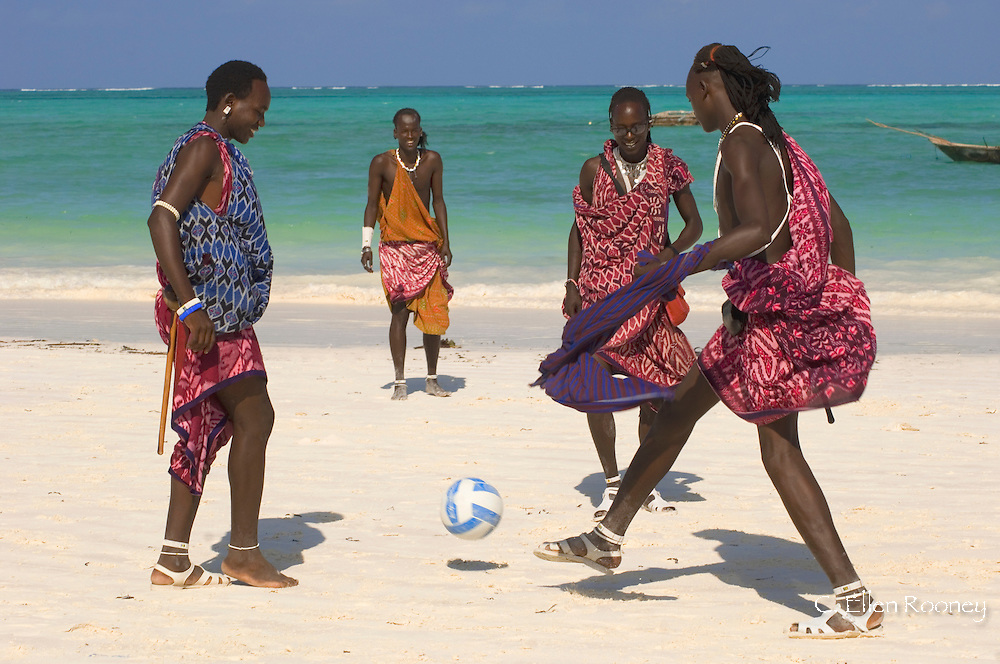 Massai tribesmen in colourful native dress playing football on the beach.<br /> Paje, Zanzibar, Tanzania